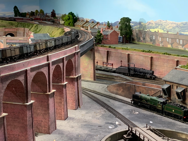 Goods train crossing viaduct over loco depot